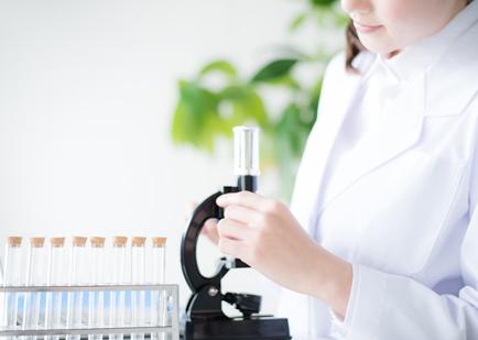 白衣の女性が顕微鏡で研究をしている